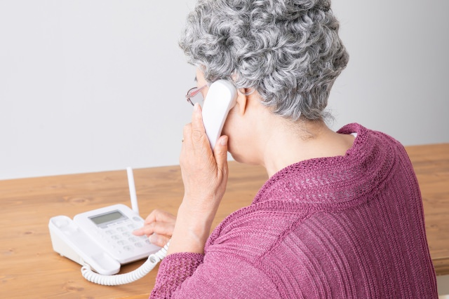 電話を受ける高齢女性